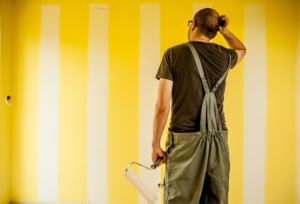 peintre devant un mur jaune